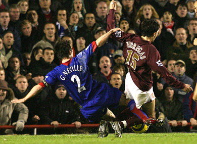 Gary Neville challenges Cesc Fabregas.