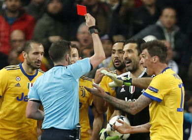 Juventus players protest as referee Michael Oliver issues a red card to Gianluigi Buffon.