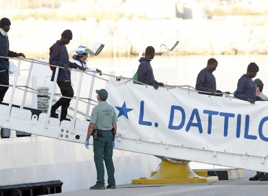 Migrants descend the Italian coast guard vessel Dattilo.