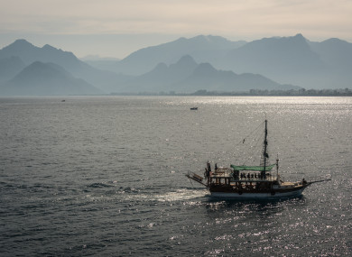 A tourist ship sails in front of a mountain landscape near Antalya, a major summer destination for tourism along Turkey's Mediterranean coast.