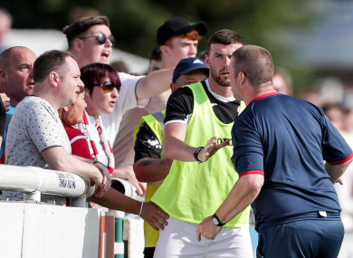 Sligo's goalkeeper coach Rodney Dalzell argues with supporters as Patrick McClean attempts to calm him.