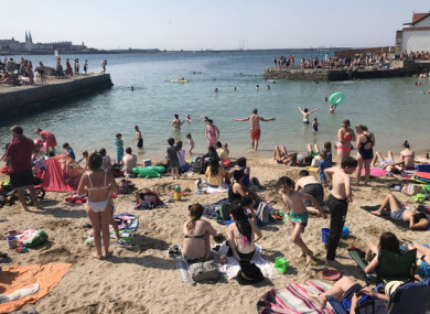 People enjoying the sunny weather on the beach on Sandycove in July.