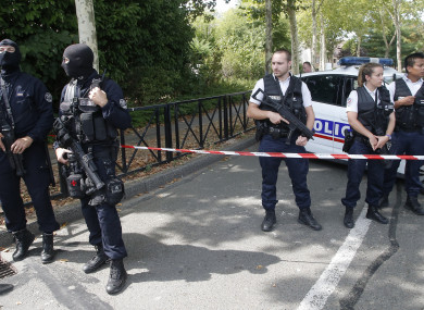 French hooded police officers guard the area with other police officers after a knife attack.