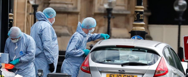 Forensics officers work near the car that crashed into security barriers outside the Houses of Parliament in London this morning.