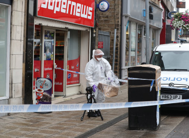 A forensic officer checks a bin in Peel Square in Barnsley town centre after a serious incident.