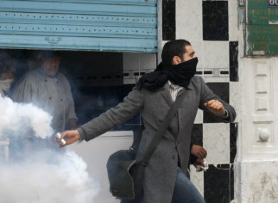 A protestor throws back tear gas at the police during clashes after a demonstration against the Constitutional Democratic Rally, RCD, party of Ben Ali in the center of Tunis, Tuesday, Jan. 18. 2011.