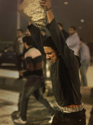 A protester throws a concrete block to the ground to break into smaller pieces to throw at riot police during clashes in downtown Cairo, Egypt, in the early hours of Wednesday, Jan. 26, 2011.
