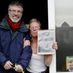 Sinn Fein's Gerry Adams gets a warm welcome from a supporter holding a picture of Michael Collins during canvassing in Drogheda, Ireland. Collins was a member of Sinn Fein but also pro-Treaty and agreed to partition so we're getting mixed messages here... Pic: Peter Morrison/AP Photos