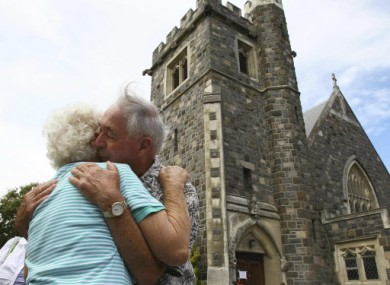 A mourning couple embrace each other in front of damaged church after observing two minutes of silence to mark the time of the earthquake.