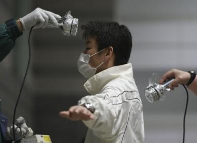 A man is screened for radiation contamination at an evacuation shelter in Koriyama, Fukushima prefecture, Japan, Saturday, April 2, 2011.