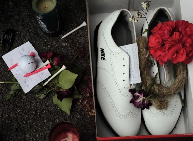 Candles and a red flower are seen beside golf shoes outside the church in Pedrena earlier.