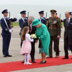 Rachel Fox, aged 8, presents the Queen with a bouquet of flowers to welcome her to the Emerald Isle. Her Majesty's choice of Emerald Green and St Patrick's Blue does not go unnoticed. (Pic: Maxwells)