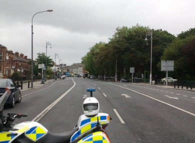 A Garda traffic motorbike holds off traffic into a deserted Fairview during an ongoing security alert there today.