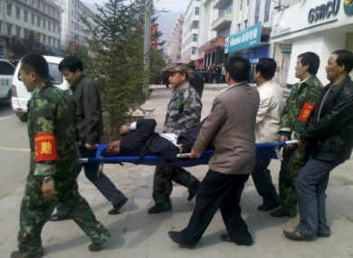 An injured person is removed from the bank in Tianzhu, China after a disgruntled former employee threw a gas bomb into the building