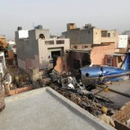 A woman looks at a small plane which crashed into a residential community in Faridabad, near New Delhi, India killing at least 10 people and injuring another two. (AP Photo/Saurabh Das)