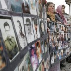 Bosnian Muslim women, survivors of the Srebrenica massacre, hold posters with photos of the missing in June 2006. <span class=