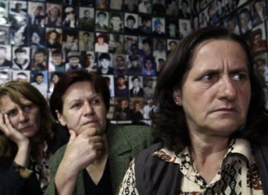 Women from Srebrenica sit in a room covered with pictures of victims of the 1995 massacre, and watch a tv broadcast of  Mladic's court proceedings at The Hague.