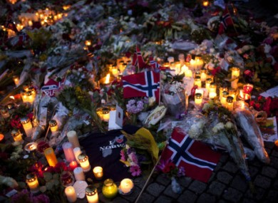 Norwegian flags, flowers and candles are seen at the ground as people gather to pay tribute to victims of the twin attacks near the Domkirke church on Friday, in central Oslo, Norway, Saturday, July 23, 2011.