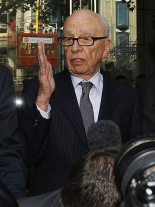 Rupert Murdoch, centre, attempts to speak to the media after he held a meeting with the parents and sister of murdered school girl Milly Dowler in London, Friday, July 15, 2011.