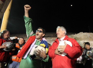 Luis Urzua (left), the last of the miners to be rescued, sings the national anthem with Chilean president Sebastian Pinera.