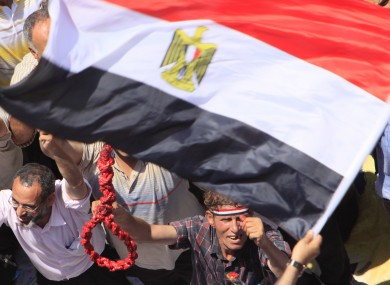An protester holds a noose under an Egyptian flag in Tahrir Square