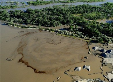 Oil swirls in a flooded gravel pit in Lockwood, Montana after crude oil pipeline ruptures in river.