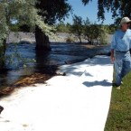 Jim Swanson is seen in his yard east of Laurel, Montana where absorbent sheets were laid down to soak up oil. (AP Photo/Matthew Brown)