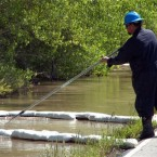 A contractor for ExxonMobil tends to an oil containment boom along the Yellowstone River near Laurel, Montana. (AP Photo/Matthew Brown)