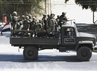 In this citizen journalism image, Syrian troops withdraw from the Damascus suburb of Saqba, Syria, on Sunday Aug. 14, 2011