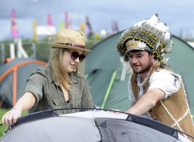 Big Chief Dago, aka Barry Davenport from Dublin, helps Brett O'Mahony from Clare put up her tent at the Electric Picnic today.