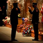 FDNY firefighters stand at a firefighters memorial at the Ten House firehouse before a ceremony.  (AP Photo/Craig Ruttle)