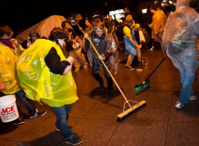 Demonstrators affiliated with the Occupy Wall Street protests sweep Zucotti park to preempt a scheduled cleanup by owners Friday morning that protestors say is a move to shut them down, Friday, Oct. 14, 2011