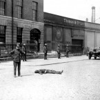 A British Soldier stands by the body of a man killed during the burning of the Custom House in Dublin on 2 May 1921 during the War of Independence. Image: Mercier Archives