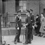 Passing women inspect the full dress uniform of Major General Brennan, Col Hayes and Col Carroll outside the Pro-Cathedral.