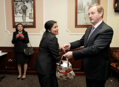 Enda Kenny holds open a bag for Maria Joseph at the Citizenship Ceremony in Dublin on Thursday.