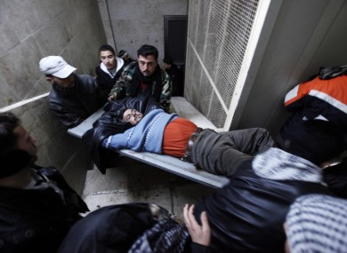 An injured Syrian rebel fighter is carried into a local hospital in Idlib, Syria