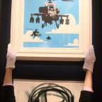 A Bonham's employee adjusts Banksy's Happy Choppers, estimated to fetch £4,000 - £6,000 at Urban Art auction. (Lewis Whyld/PA Images)