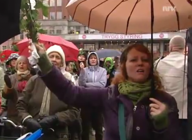 A woman holds a rose as she sings along to 'Barn av regnbuen' at Youngstorget in Oslo.