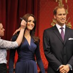 The new wax figures of the Duke and Duchess of Cambridge are given a final comb of the hair by make-up artist Rebecca Holmes before they go on display. (John Stillwell/AP Images)