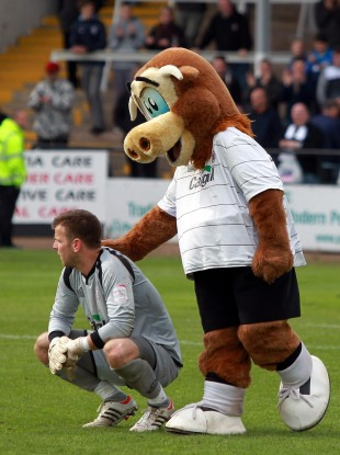 Hereford goalkeeper is comforted by the club mascot after their relegation.