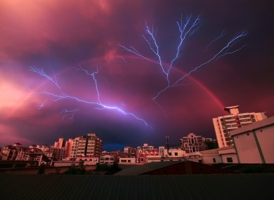 Lightning and a rainbow appear simultaneously during a storm in Haikou, China