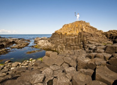 Torchbearer Peter Jack carrying the flame at the Giant's Causeway yesterday.
