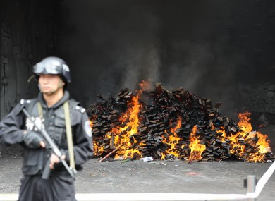 An officer guards a burning pile of guns in Yuxi, Tunnan Province.