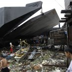 Residents try to salvage pieces of their homes after two empty barges rammed into shanties on stilts at a poor community in Manila yesterday. (AP Photo/Aaron Favila/PA)