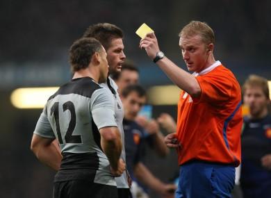 Referee Wayne Barnes gives Luke McAlister a yellow card in 2007.