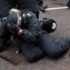 A female police officer is knocked to the ground as she attempted to stop fighting rival groups outside St Patrick's. (AP Photo/Peter Morrison/PA)