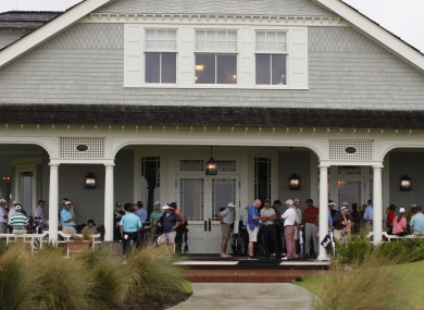 Golfers wait out the rain on the clubhouse porch during a weather-delayed practice round at the PGA Championship golf tournament on the Ocean Course of the Kiawah Island GC.
