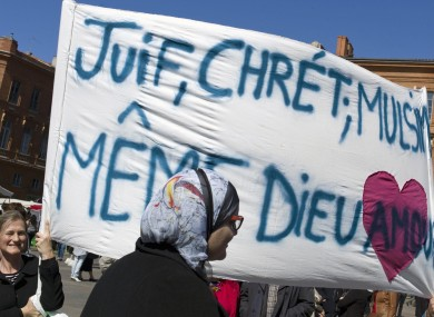 People gather to pay their respects to the shooting victims of Mohamed Merah in Toulouse. Banner reads: