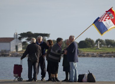Residents with Croatian flag wait for a boat in Gen. Ante Gotovina's hometown of Pakostane, southern Croatia, Friday, Nov. 16, 2012.
