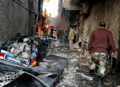 A Syrian soldier, right, and citizens gather at an alley that was destroyed by two cars bombs, at Jaramana neighborhood, in the suburb of Damascus.